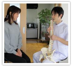 お客さまに体についてのアドバイスをする整体師